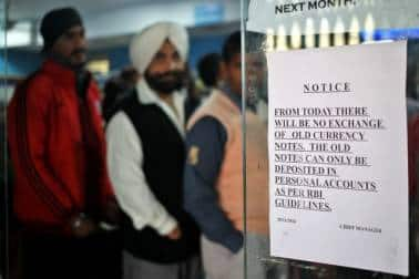 A notice is displayed at the entrance of a bank stating the end of the exchange of old high denomination banknotes, as people queue to deposit their old high denomination banknotes in Jammu, November 25, 2016. REUTERS/Mukesh Gupta - RC11DBB16CE0
