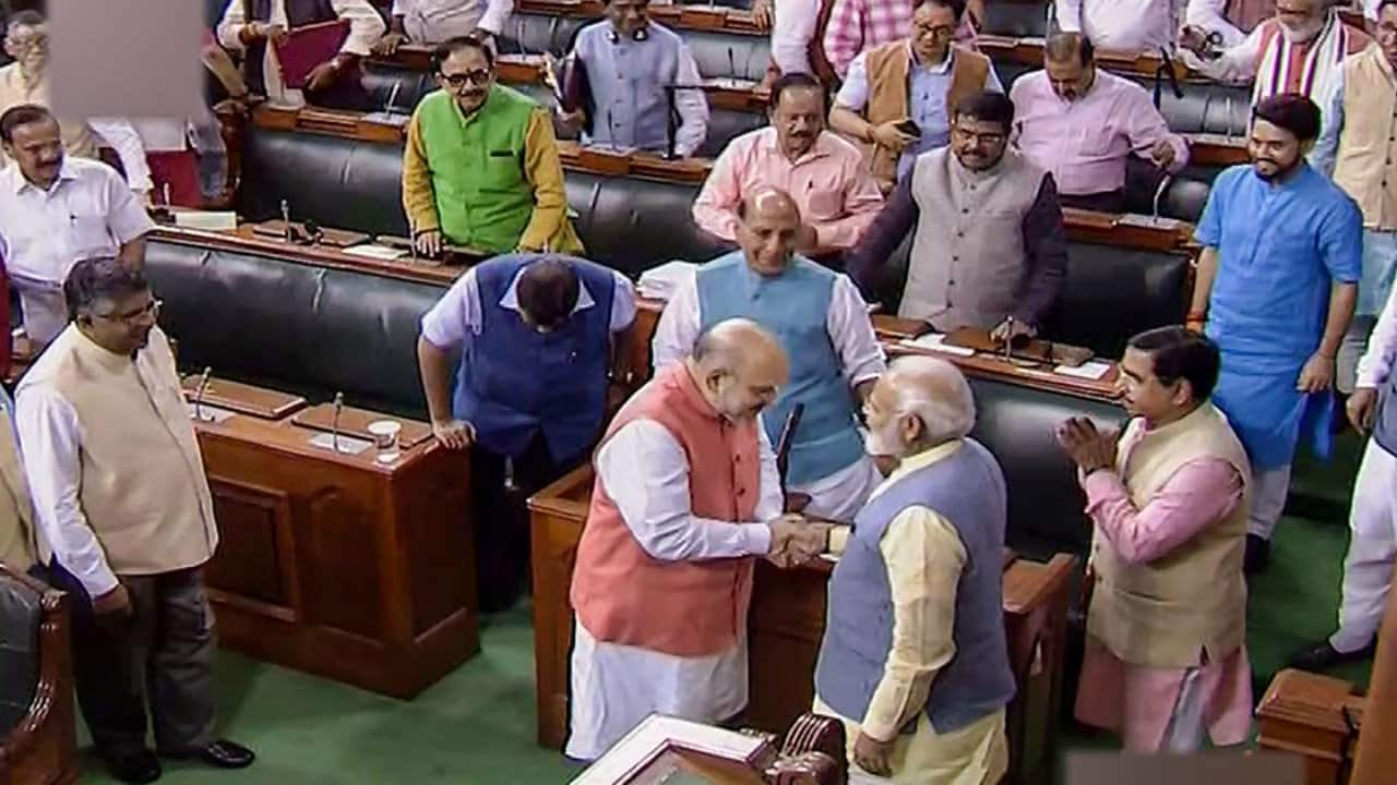 Home Minister Amit Shah is seen with PM Modi after a Bill to bifurcate J&K was passed in Lok Sabha. (Image: PTI)