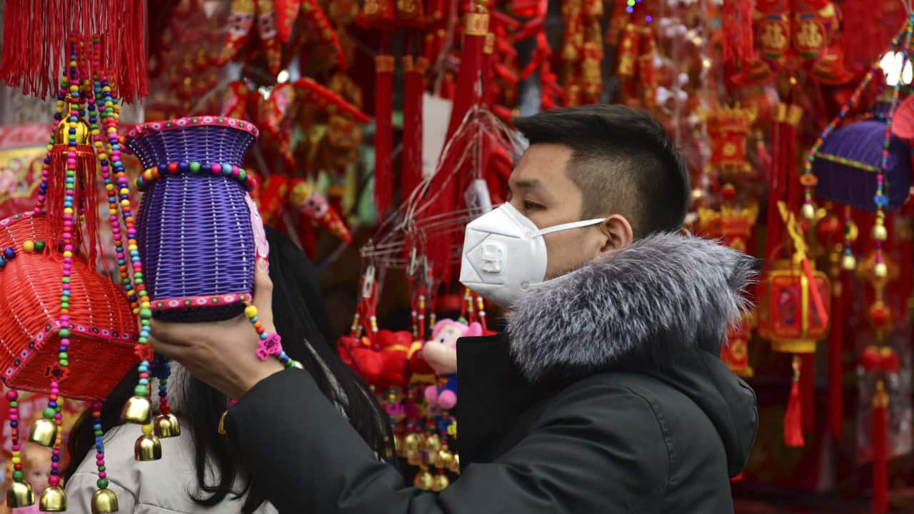 A man wears a face mask as he shops for decorations for the upcoming Lunar New Year, the Year of the Rat, at a market in Fuyang in central China's Anhui Province. China closed off a city of more than 11 million people Thursday in an unprecedented effort to try to contain a deadly new viral illness that has sickened hundreds and spread to other cities and countries in the Lunar New Year travel rush. (Image: Associated Press)