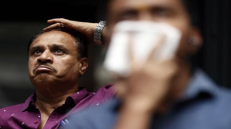 A man reacts as he looks at a screen displaying the Sensex results outside the Bombay Stock Exchange building, Mumbai, March 12. REUTERS