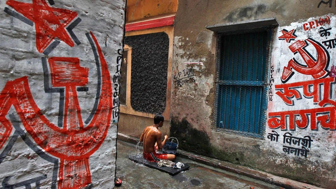 A man bathes in an alley with walls painted with the party symbol of the Communist Party of India (Marxist) in Kolkata (Image: Reuters)