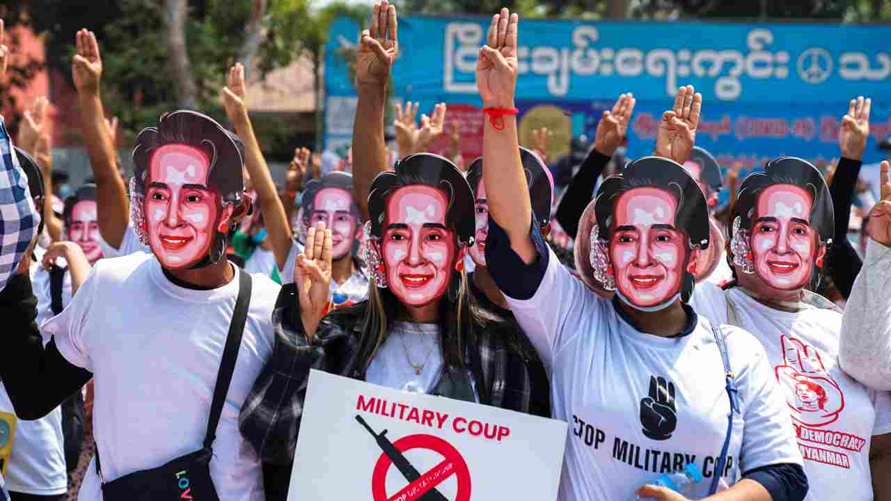 Protesters wearing masks depicting ousted leader Aung San Suu Kyi, flash three-finger salutes as they take part in a protest against the military coup in Yangon, Myanmar. (Image: Reuters)