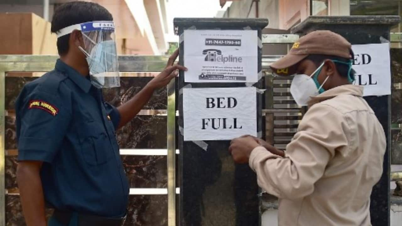 A security guard puts up a notice informing the non-availability of beds for patients in a private hospital amid COVID-19 surge in Allahabad, Uttar Pradesh on April 22, 2021. (Image: Sanjay Kanojia/AFP)