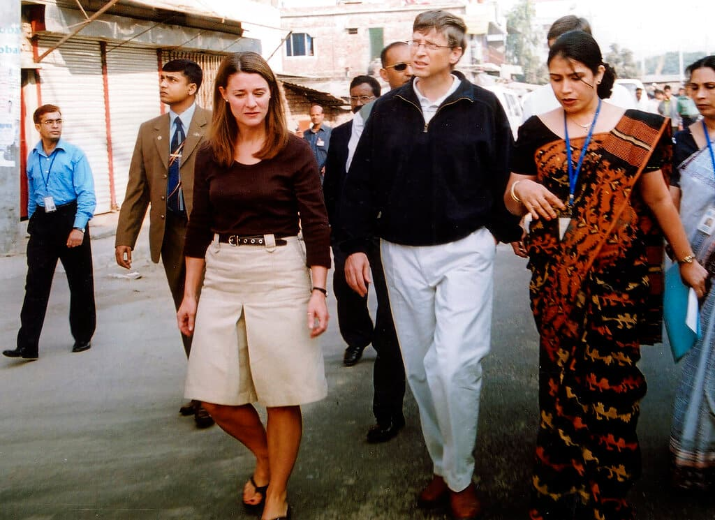 In this December 5, 2005, file photo, Bill Gates, founder and chairman of Microsoft Corp., center, and his wife Melinda, left, walk on a street in Dhaka, Bangladesh. (Image: AP)