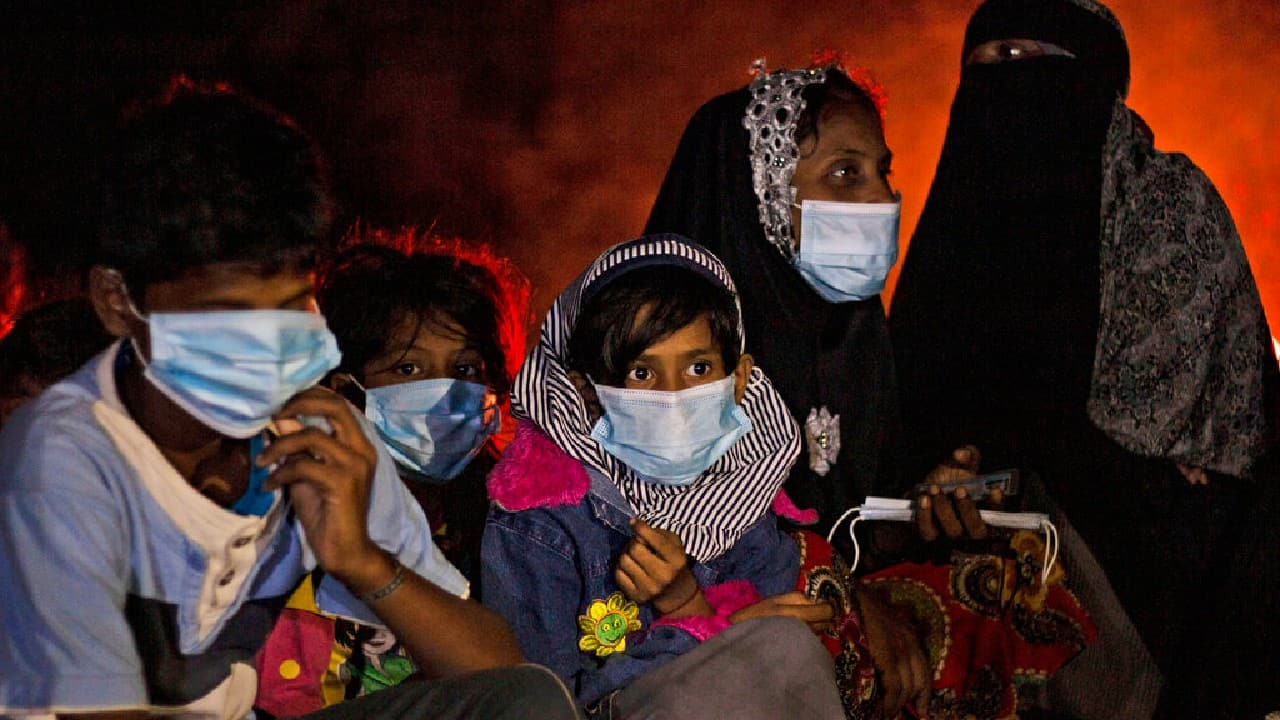 Ethnic Rohingya women and children sit by a fire on a beach after their boat was stranded on Idaman Island in East Aceh, Indonesia, June 4, 2021. Villagers in Indonesia's Aceh province discovered a stranded boat carrying dozens of Rohingya Muslims, including children, who had left a refugee camp in Bangladesh, officials said. (Image: AP/Zik Maulana)