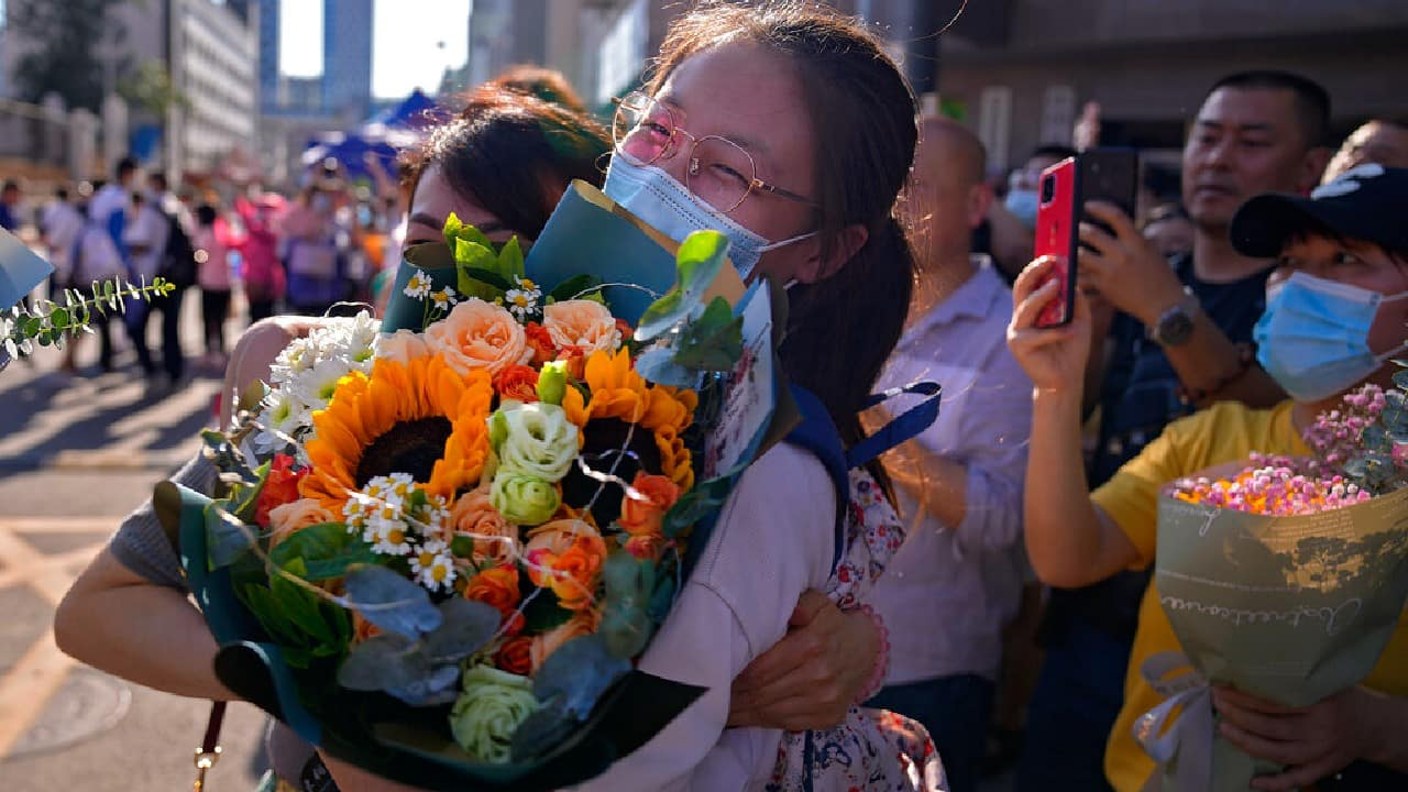 A student wearing a face mask to help curb the spread of the coronavirus with a bouquet of flowers is hugged by her relative at the end of China's national college entrance examinations, known as the gaokao in Beijing, June 10, 2021. Millions of students took part in the tough annual exams from which the results determine entrance to the country's top universities. (Image: AP/Andy Wong)