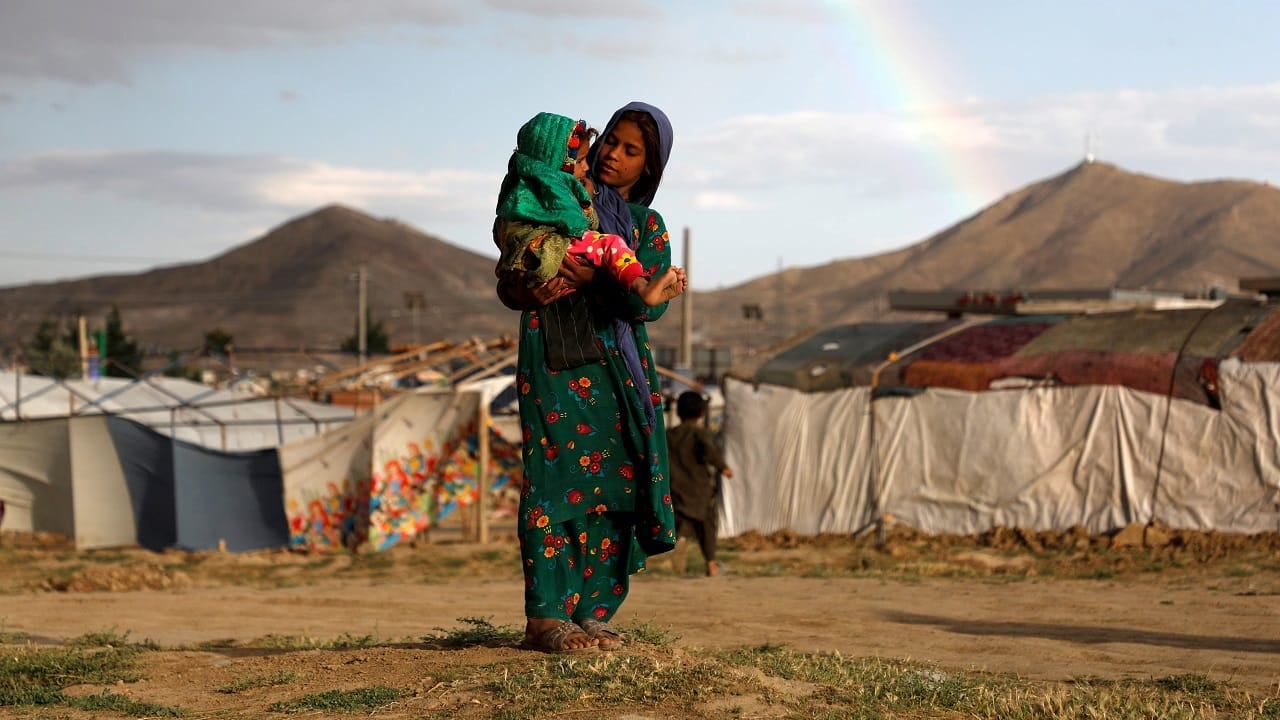 An internally displaced Afghan girl carries a child near their shelter at a refugee camp on the outskirts of Kabul on June 20, 2019 (Image: Reuters/Omar Sobhani)