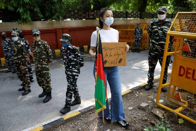 An Afghan woman holds a placard as she stands next to Indian security forces during a protest demanding international community to help Afghan refugees, in New Delhi, India, August 23, 2021. REUTERS/Adnan Abidi - RC2XAP9QS1ON